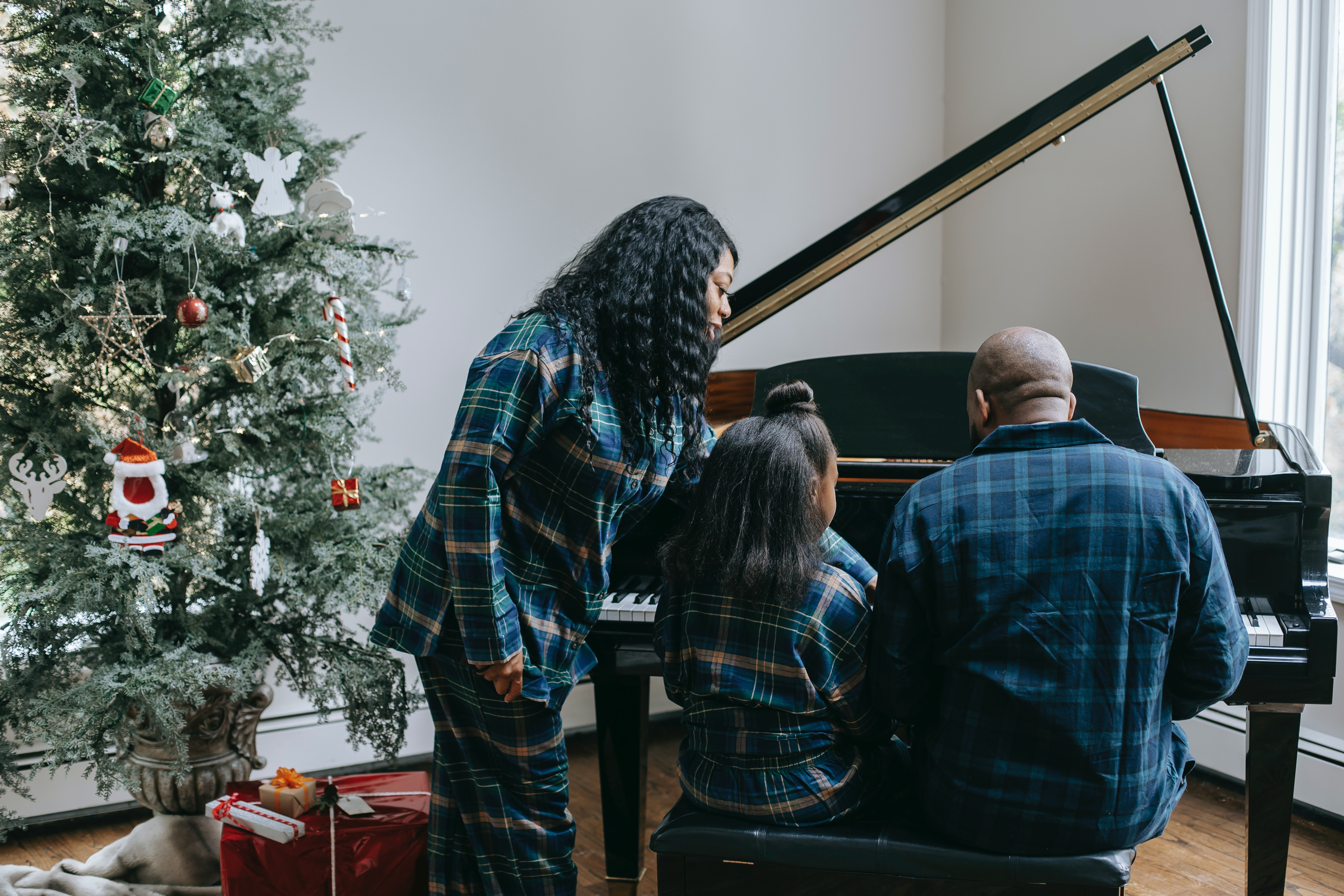 A child with her parents playing the piano